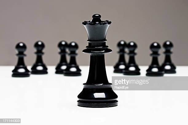 Chess queen stands in front of pawns
