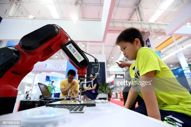 A chess robot plays chess with a boy during the 2017 World Robot Conference at Beijing Yichuang International Conference and Exhibition Center on...