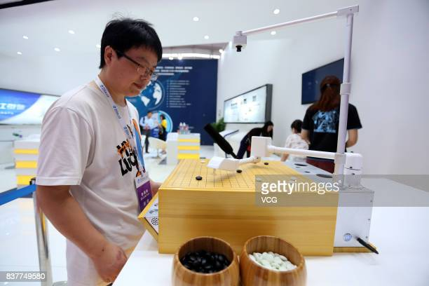 A chess robot plays chess with a visitor during the 2017 World Robot Conference at Beijing Yichuang International Conference and Exhibition Center on...