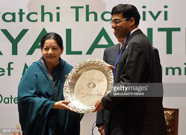 Chess runnerup Vishwanathan Anand receives a trophy from the Chief Minister of Tamil Nadu J Jayalalithaa during a presentation ceremony in Chennai on...