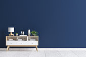 Chest of drawers in living room interior, dark blue wall mock up background, 3D render