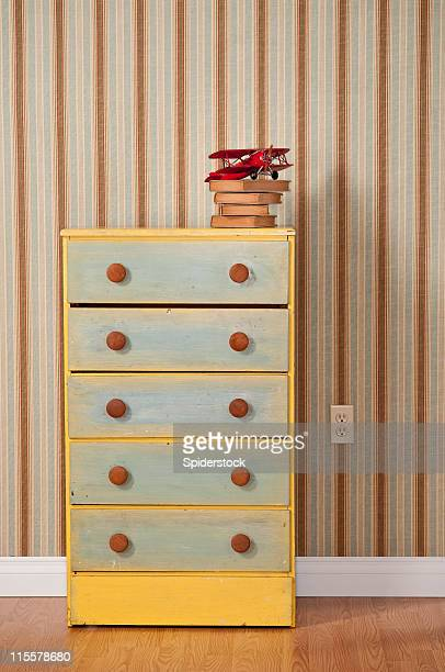 Chest Of Drawers With Books in Empty Bedroom