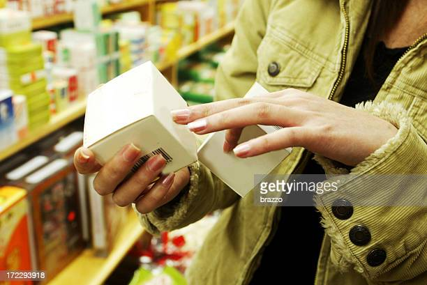 Chest view of a female shopper looking at a cosmetic box