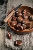 Chestnuts in wooden bowl, knife on top
