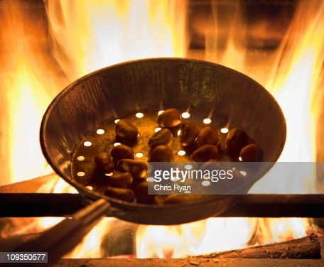 Chestnuts roasting in a pan on fire : Stock Photo