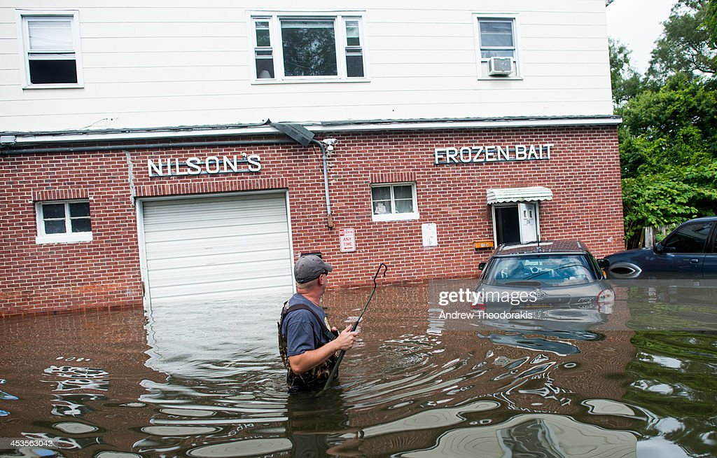 Chet Hingle wades in the water in front of his home on a flooded Reddington St. following heavy rains and flash flooding August 13, 2014 in Bayshore, New York. The south shore of Long Island along with the tri-state region saw record setting rain that caused roads to flood entrapping some motorists.