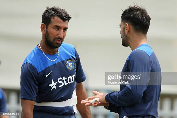 Cheteshwar Pujara speaks to teammate Virat Kohli during a training session for the Indian cricket team at Gliderol Stadium on November 23 2014 in...