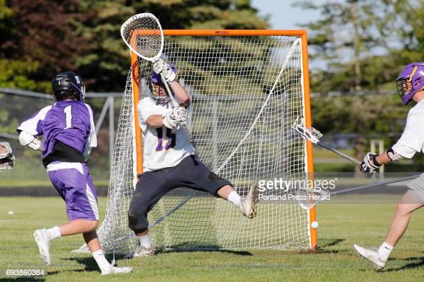Cheverus goalie senior Sean Walsh fends off a shot from Deering junior Jonah Peterson during their quarterfinal game at Cheverus High School Cheverus...