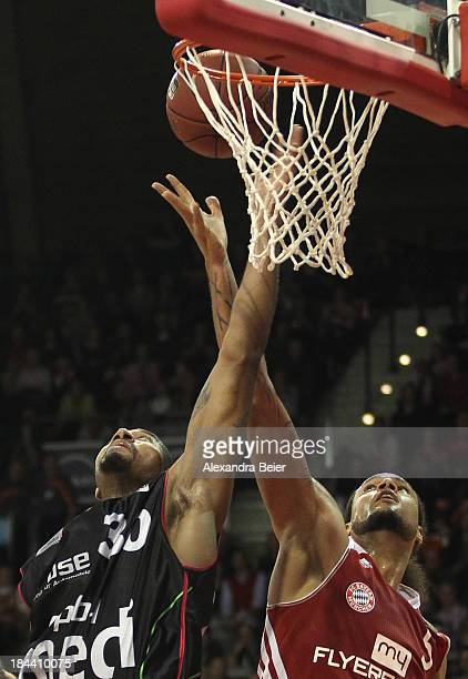 Chevon Troutman of Bayern Muenchen jumps for the ball with Ronald Burrell of medi Bayreuth during the Basketball Bundesliga match between FC Bayern...