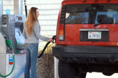 Chevron customer pumps gasoline into her Hummer at a chevron service station on January 25 2011 in San Rafael California Gas prices continue to rise...