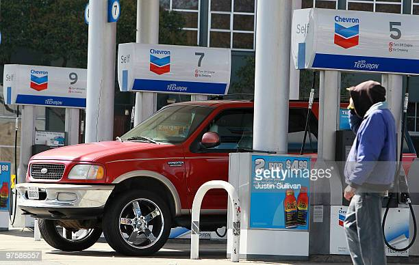 Chevron customer walks by gas pumps at a Chevron gas station March 9 2010 in San Francisco California Chevron Corp announced that it would cut 2000...