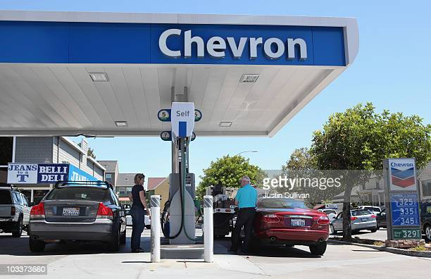 Chevron customers pump gas into their cars at a Chevron gas station August 13 2010 in San Rafael California US retail sales rose 04 percent in July...