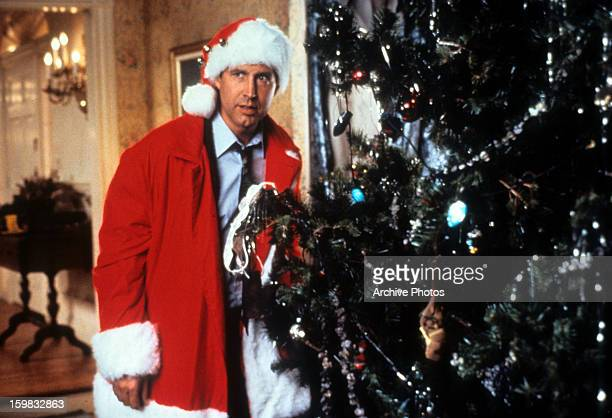 Chevy Chase hides behind the tree in a scene from the film 'Christmas Vacation' 1989
