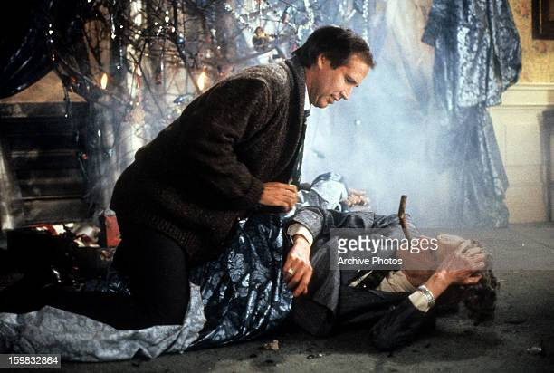 Chevy Chase sits over a man in a scene from the film 'Christmas Vacation' 1989