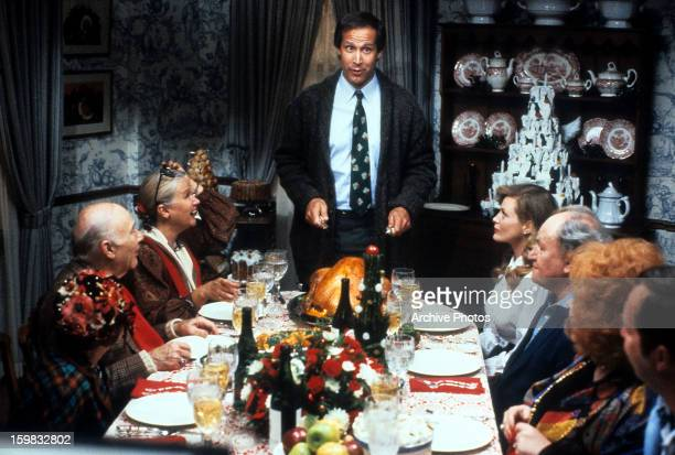 Chevy Chase stands at the head of the table in a scene from the film 'Christmas Vacation' 1989