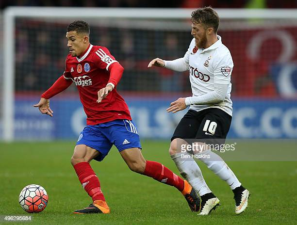 Cheye Alexander of Aldershot holds off pressure from Billy Clarke of Bradford during The Emirates FA Cup First Round match between Aldershot Town and...