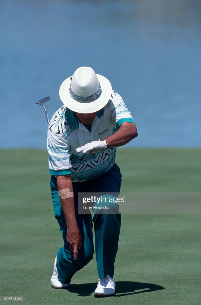 Chi Chi Rodriguez pretends to sheathe his putter after sinking a shot.