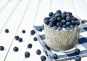 Chia pudding with blueberries on striped canvas, white wood background