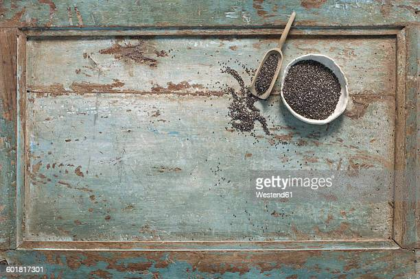 Chia seeds in bowl, shovel on wood