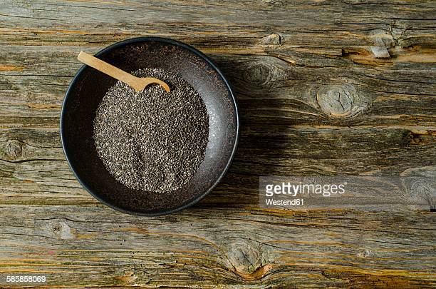 Chia seeds with a wooden spoon in a bowl