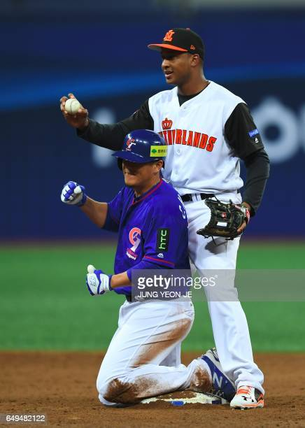 Chiang ChihHsien of Taiwan reacts after sliding into second before infielder Jonathan Schoop of the Netherlands tags him during the third inning of...