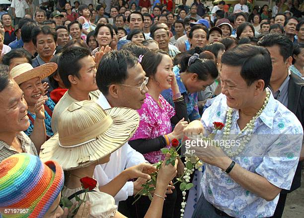 Thai Prime Minister Thaksin Shinawatra receives flowers from his supporters during a visit to a temple in Chiang Mai province 28 March 2006 Thai...