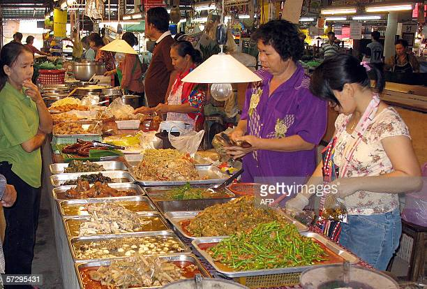 Thai vendors take orders for their cooked food in one of the main market in the hometown of Thailand's caretaker Prime Minister Thaksin Shinawatra in...