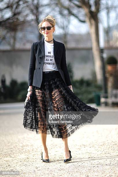 Chiara Ferragni wears sunglasses a black blazer jacket a white tshirt with the inscriptions ' We should all be Feminists' a black meshed dress black...