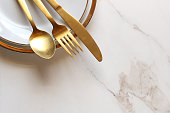 Modern gold and white place setting frames ample white marble copy space.