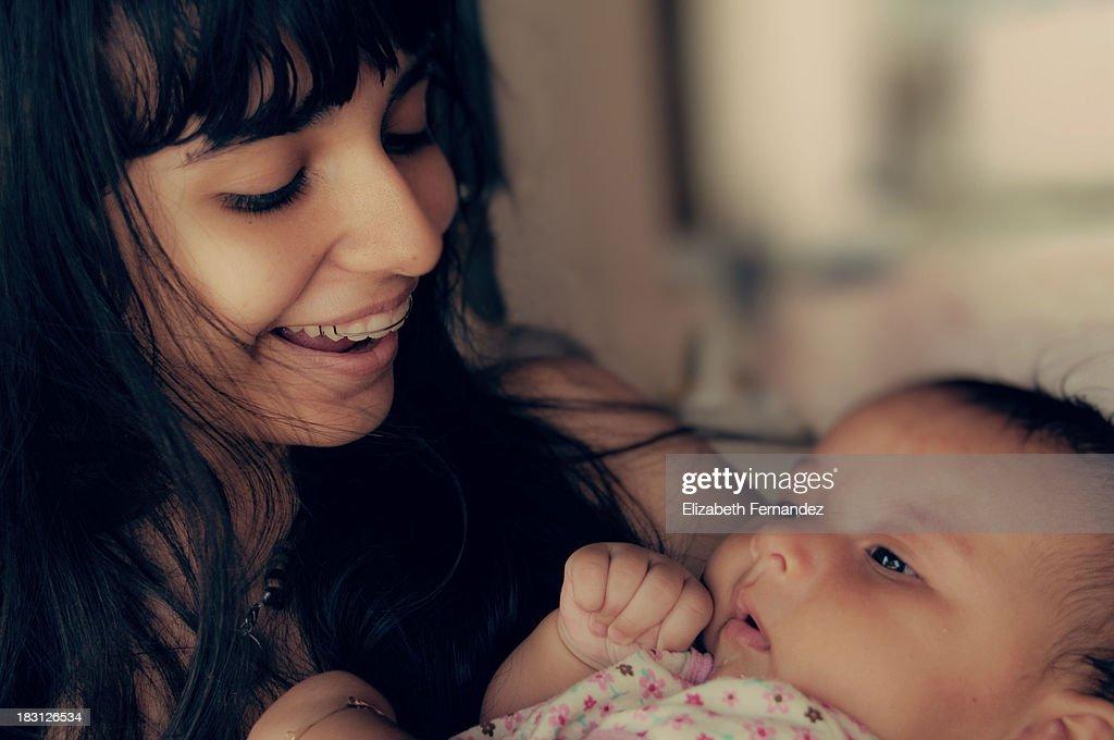 Chica adolescente cargando en sus brazos a bebé