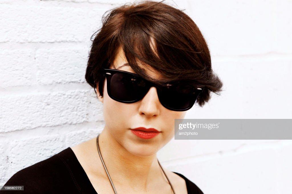 Chica seria con gafas de sol : Stock Photo