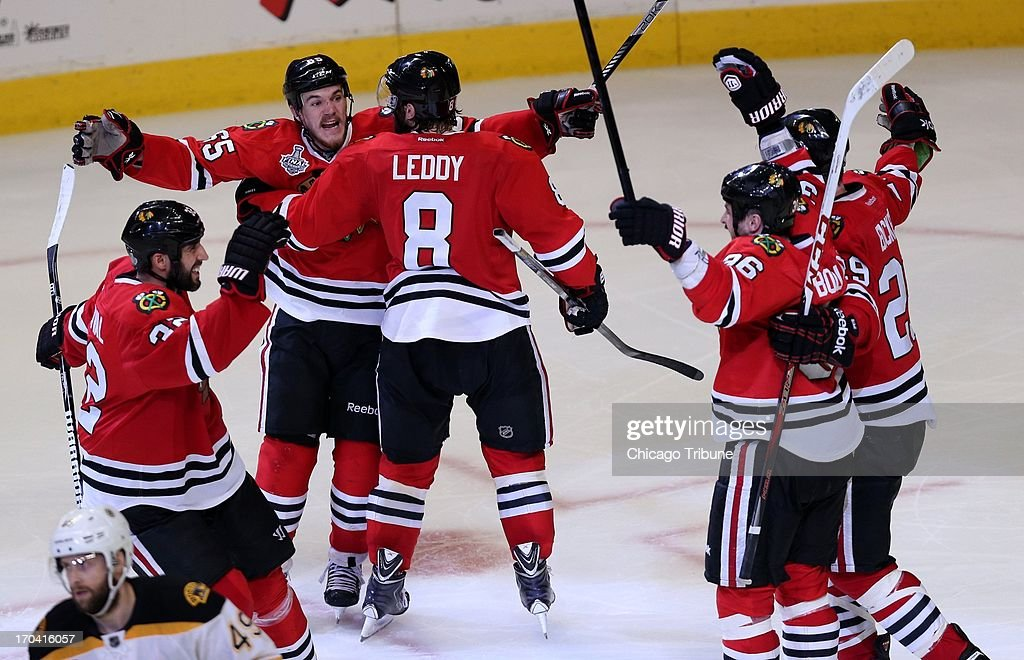 Chicago Blackhawks' Andrew Shaw, second from left, celebrates with teammates after scoring the winning goal in a third overtime against the Boston Bruins in Game 1 of the NHL Finals on Wednesday, June 12, 2013, at the United Center in Chicago, Illinois.