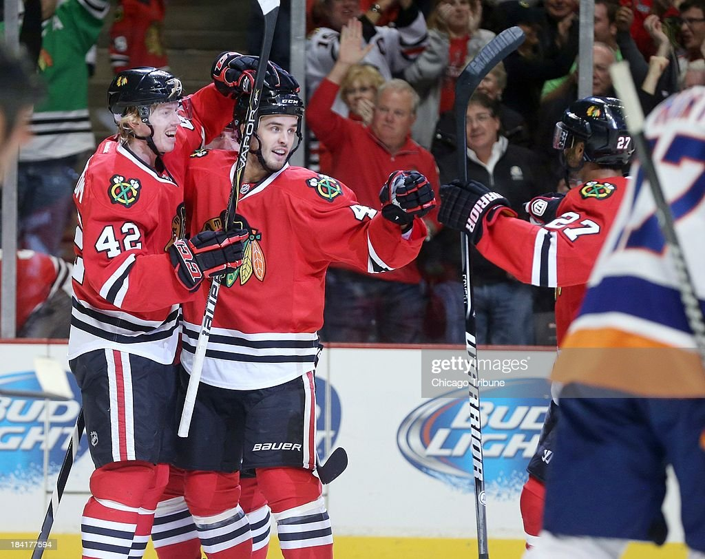 Chicago Blackhawks center Joakim Nordstrom (42) celebrates his first career goal with teammate Niklas Hjalmarsson (4) in the first period against the New York Islanders at the United Center in Chicago, Illinois, Friday, October 11, 2013. The Blackhawks beat the Islanders, 3-2.