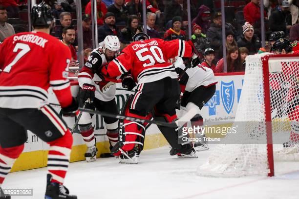 Chicago Blackhawks goalie Corey Crawford guards Arizona Coyotes left wing Jordan Martinook and Arizona Coyotes center Brad Richardson during the...