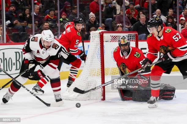 Chicago Blackhawks goalie Corey Crawford guards the net while Arizona Coyotes center Brad Richardson and Chicago Blackhawks right wing Tommy Wingels...