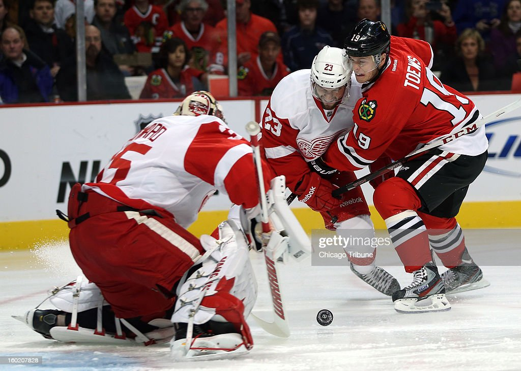 Chicago Blackhawks' Jonathan Toews battles Detroit Red Wings' Brian Lashoff as Jimmy Howard makes a save during 1st-period action at the United Center in Chicago, Illinois, Sunday, January 27, 2013.