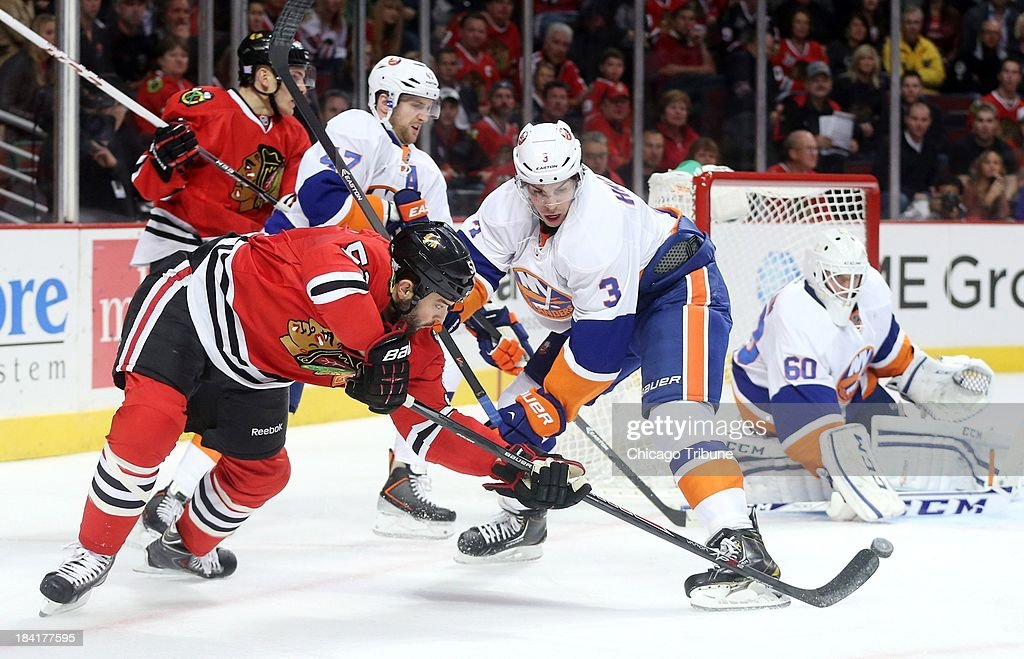 Chicago Blackhawks left wing Brandon Bollig (52) takes a shot while defended by New York Islanders defenseman Travis Hamonic (3) in the first period at the United Center in Chicago, Illinois, Friday, October 11, 2013. The Blackhawks beat the Islanders, 3-2.