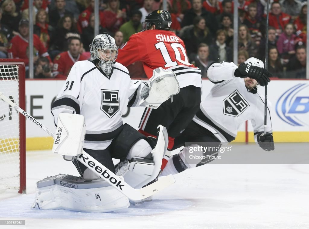 Chicago Blackhawks left wing Patrick Sharp (10) is squeezed between Los Angeles Kings goalie Martin Jones (31) and Los Angeles Kings defenseman Drew Doughty (8) during the first period at the United Center in Chicago on Monday, Dec. 30, 2013.