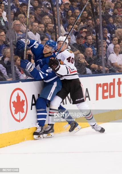 Chicago Blackhawks right wing John Hayden battles along the boards with Toronto Maple Leafs defenseman Nikita Zaitsev in the first period during the...