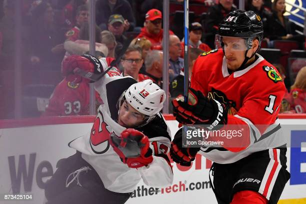 Chicago Blackhawks right wing Richard Panik slams New Jersey Devils center Nico Hischier against the boards during the game between the New Jersey...