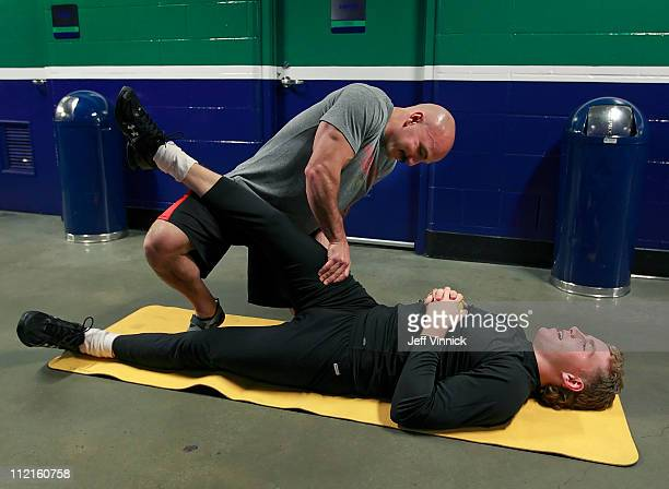 Chicago Blackhawks strength and conditioning coach Paul Goodman helps Patrick Kane of the Chicago Blackhawks stretch before Game One of the Western...