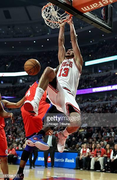 Chicago Bulls center Joakim Noah dunks over Philadelphia 76ers small forward Dorell Wright in the first half at the United Center in Chicago Illinois...