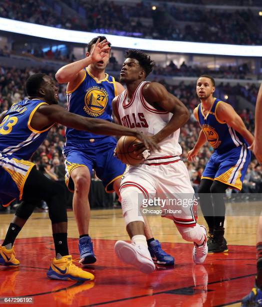 Chicago Bulls forward Jimmy Butler is defended by Golden State Warriors forward Draymond Green center Zaza Pachulia and guard Stephen Curry during...