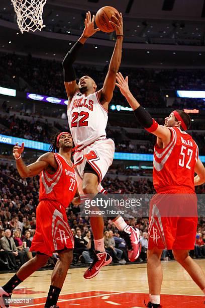 Chicago Bulls forward Taj Gibson drives to the basket between Houston Rockets forward Jordan Hill and Houston Rockets center Brad Miller during the...