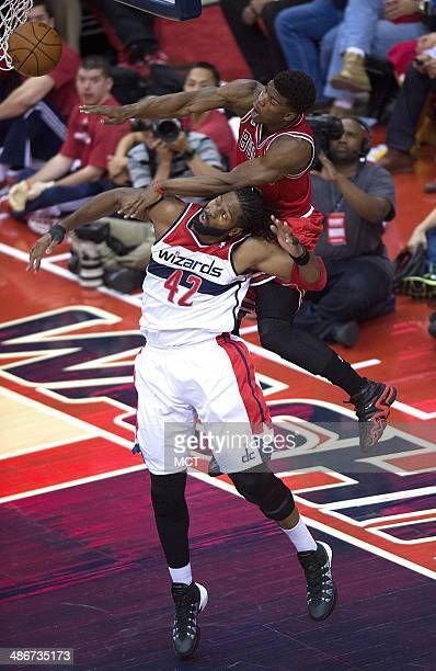 Chicago Bulls guard Jimmy Butler tries to grab a rebound over the back of Washington Wizards forward Nene Hilario during the first half of their...