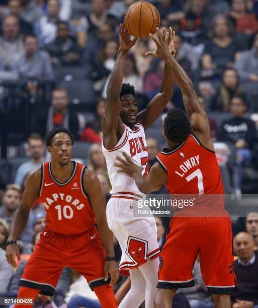 Chicago Bulls guard Justin Holiday looks to pass over Toronto Raptors guard Kyle Lowry with Toronto Raptors guard DeMar DeRozan on the other side...