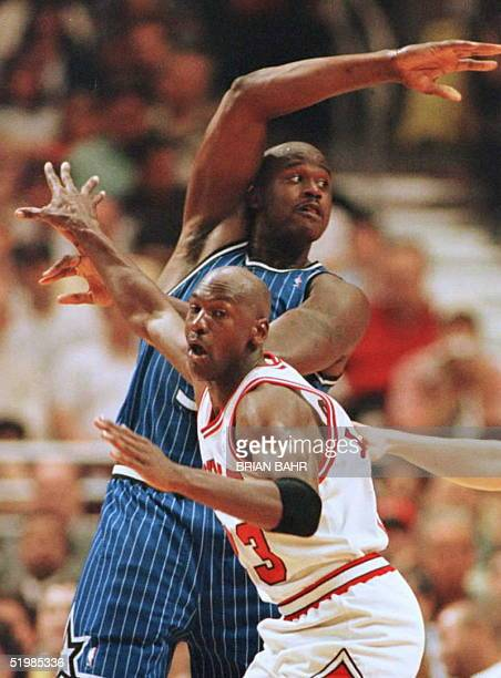 Chicago Bulls guard Michael Jordan and Orlando Magic center Shaquille O'Neal battle for position under the Orlando basket 19 May during the second...