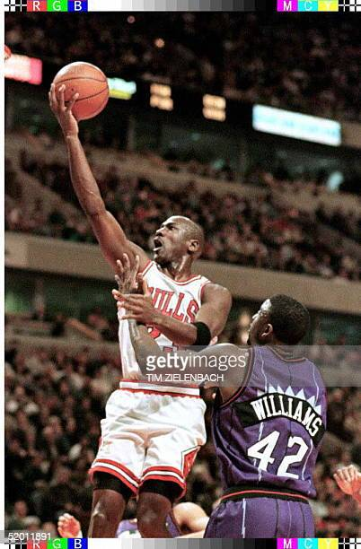 Chicago Bulls guard Michael Jordan drives past Toronto Raptors forward Walt Williams for a basket in the first quarter 25 January at the United...