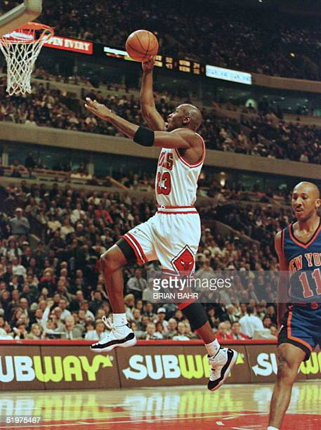 Chicago Bulls' guard Michael Jordan flies to the net on a fast break as New York Knicks guard Derek Harper fails to give chase in the first quarter...