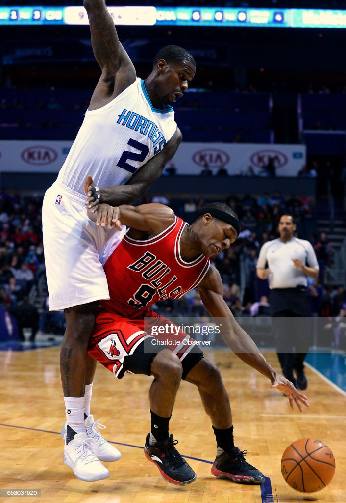 Chicago Bulls guard Rajon Rondo, right, attempts to maintain control of the ball while being fouled by Charlotte Hornets forward Marvin Williams, left, during first half action on Monday, March 13, 2017 at the Spectrum Center in Charlotte, N.C.